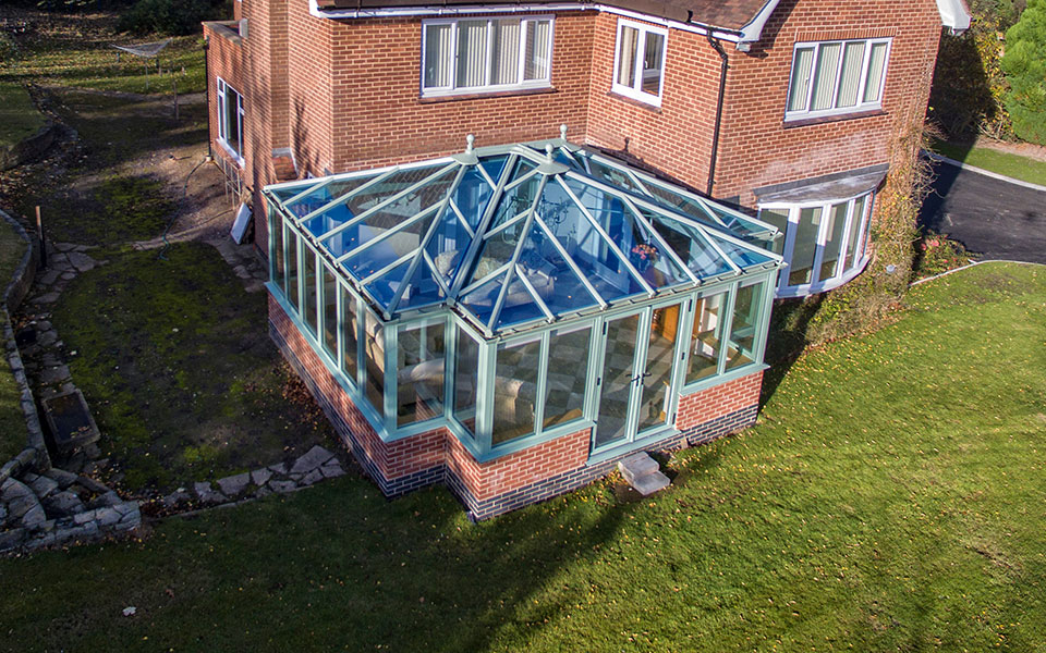 Chartwell green uPVC T-Shaped conservatory with a glass roof